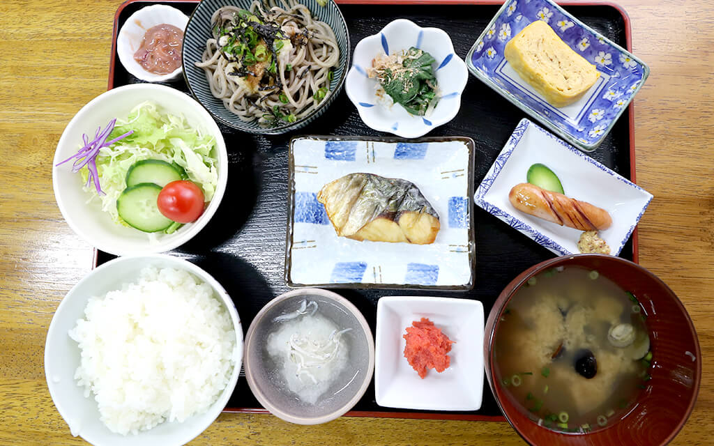 焼魚、サラダ、蕎麦、卵焼きなどバラエティ豊かな朝食の膳